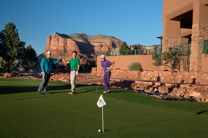 group of golfers celebrate a made putt